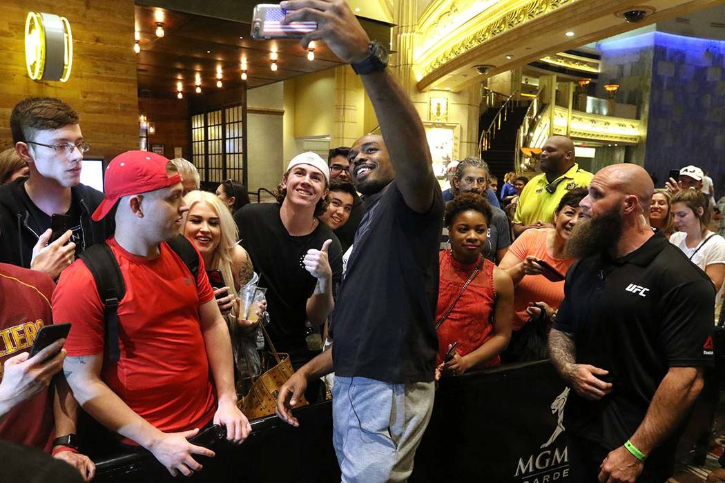 UFC light heavyweight champion Jon Jones holds up a cell phone to take a picture with a fan at ...