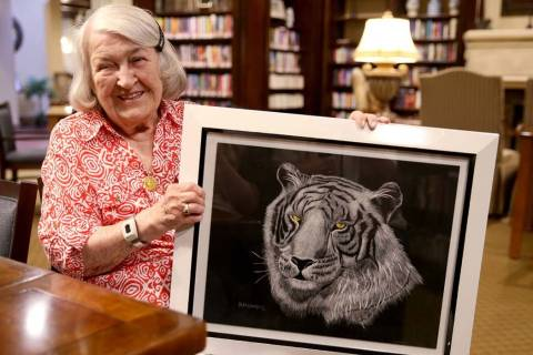Artist Hannelore Lowrey shows one of her pieces in the library of her living facility Wednesday ...