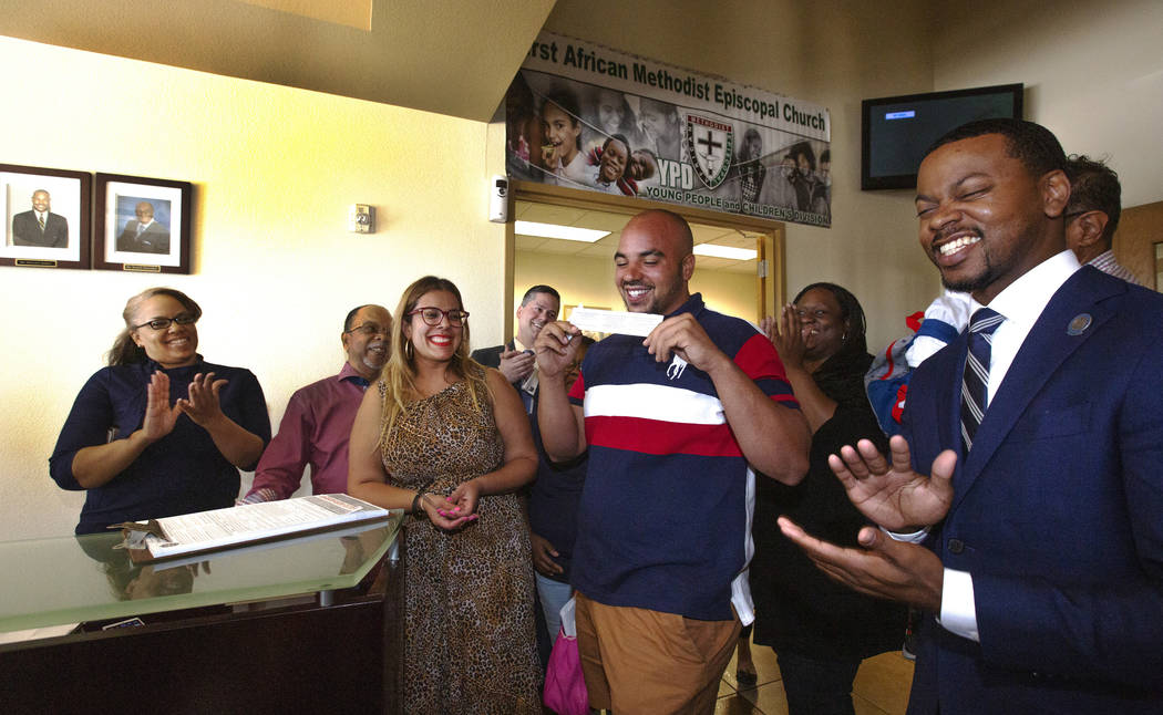 Jovan Jackson, 27, center, holds up his voter ID after signing the paperwork to register to vot ...