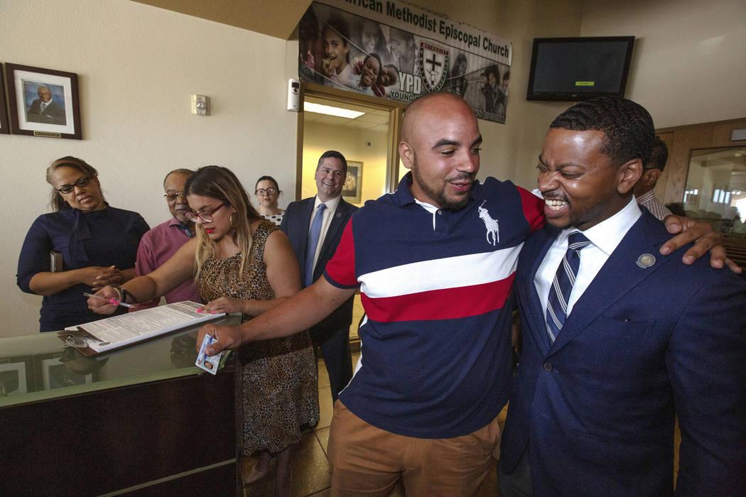 Jovan Jackson, 27, center, hugs Nevada Legislator William O. McCurdy II, right, after Jackson r ...