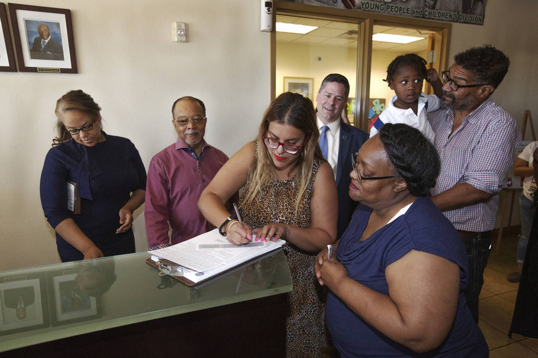 Ora Watkins, right, looks on as she receives help with her voter registration from Emily Zamora ...