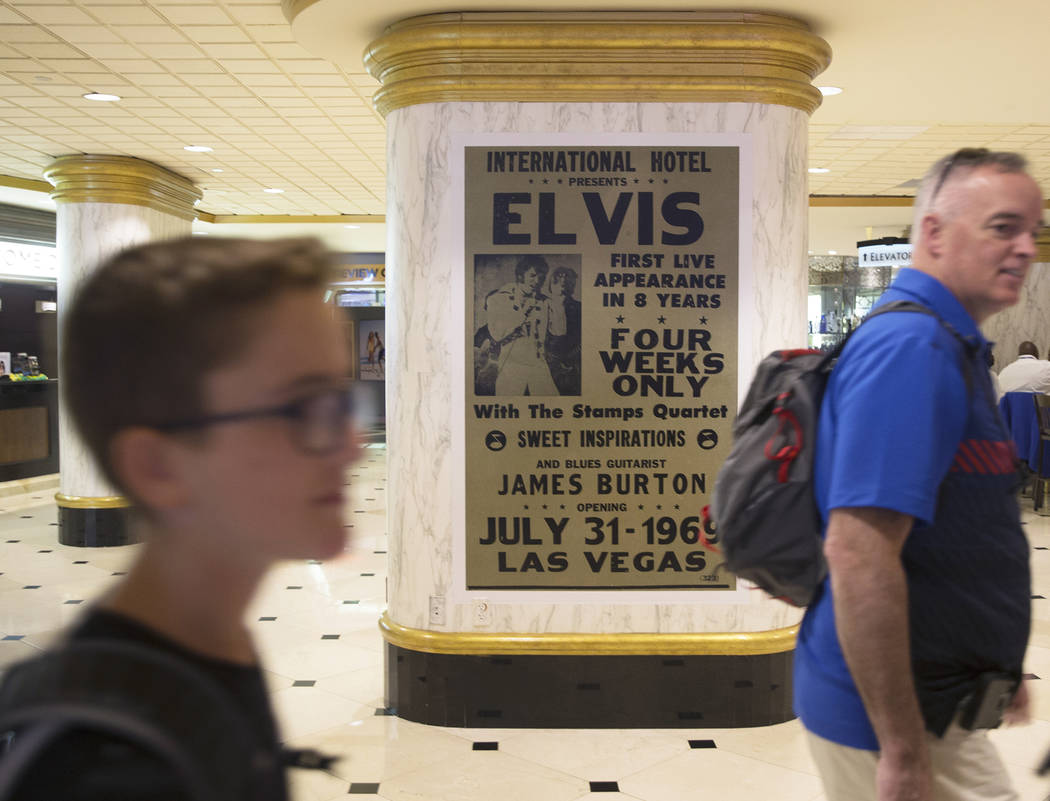 Guests pass a commemorative plaque celebrating Elvis Presley's shows at the International Hotel ...
