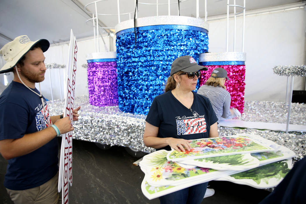 "Julien Mihy, left, and Kelly Cawood work on the ""Mary Poppins Jolly Holiday"" float during a med ..."
