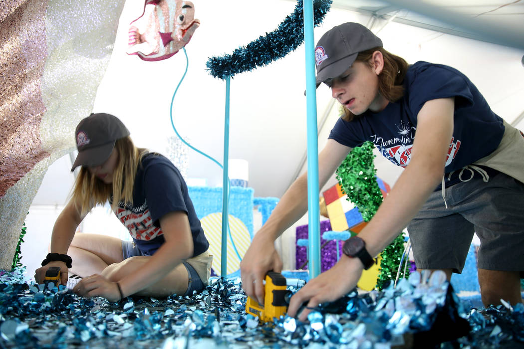 "Jordyn Doyle, left, and Noah Jordan work on the ""Undersea Jubilee"" float during a media preview ..."