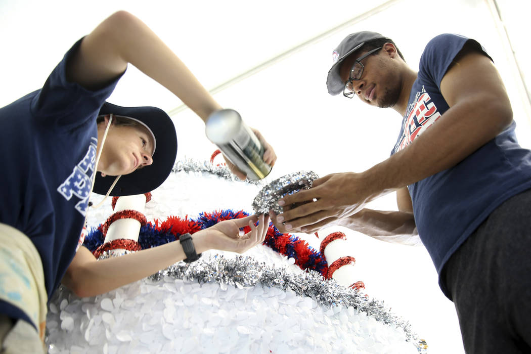 Connor Jordan, left, and Dwight Jones work in the Happy Birthday America float during a media p ...
