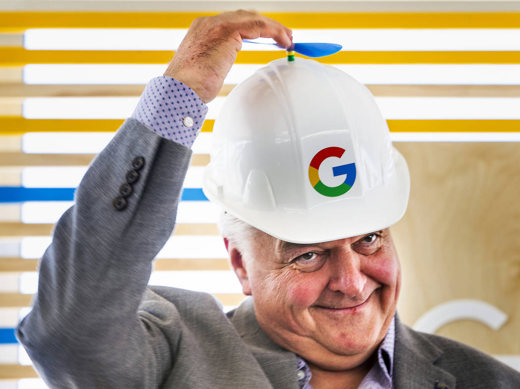 Gov. Steve Sisolak spins the little propeller atop his Google hard hat before a ceremonial dirt ...