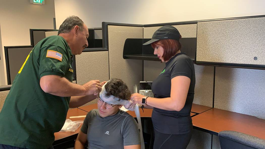 Silvia Romero, right, helps bandage the head of an attendee at the CERT training class on Satur ...