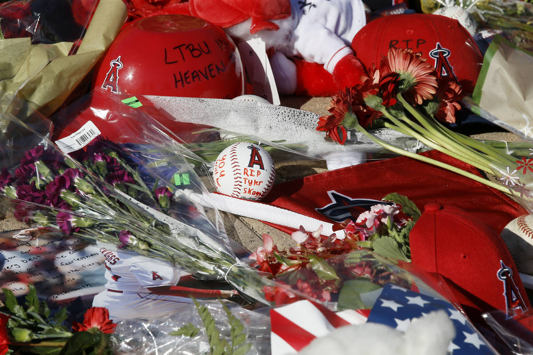 Los Angeles Angel fans place flowers, hats and mementos for pitcher Tyler Skaggs at Angel Stadi ...