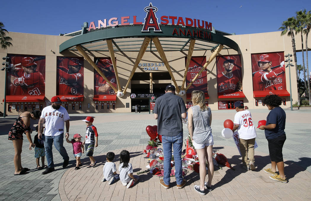Mourners stand at a memorial to give their condolences for Los Angeles Angels pitcher Tyler Ska ...