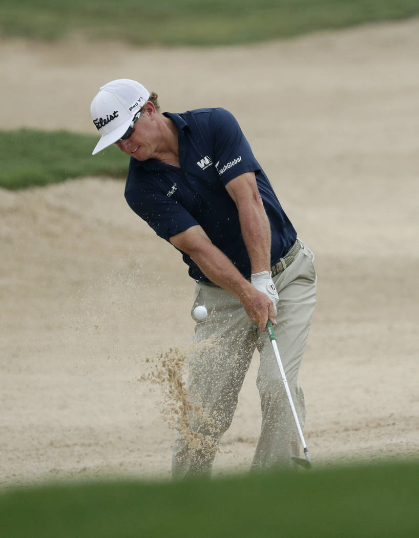 Charley Hoffman plays a shot from a bunker on the 14th hole during the third round of the Texas ...
