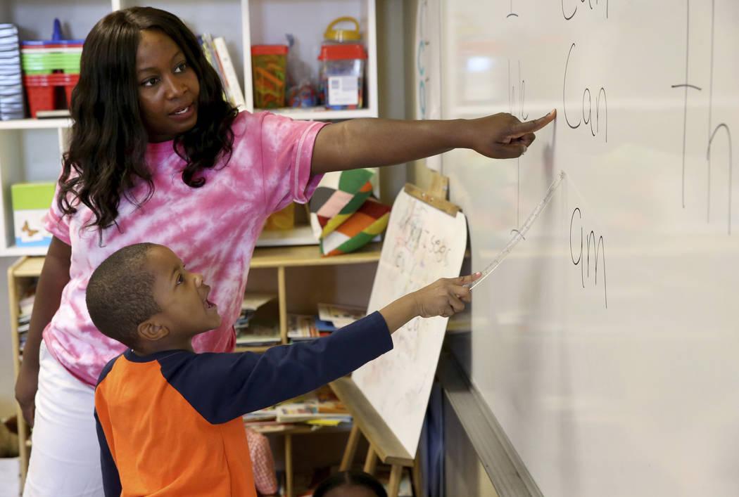 Kindergarten teacher Mo Fasehun and Joseph Dean work on sentences in her classroom during summe ...
