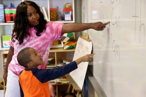 Kindergarten teacher Mo Fasehun and Joseph Dean work on sentences in her classroom during summe ...