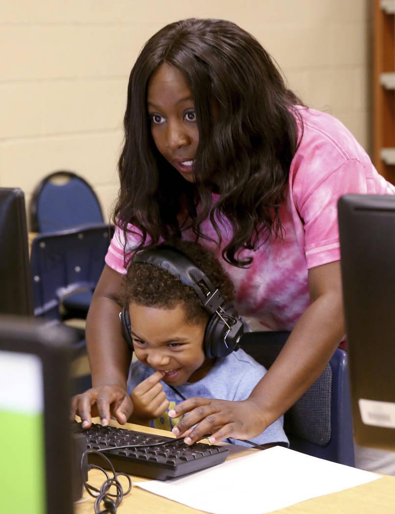 Kindergarten teacher Mo Fasehun prepares Carmello Washington to take a test in the library at 1 ...