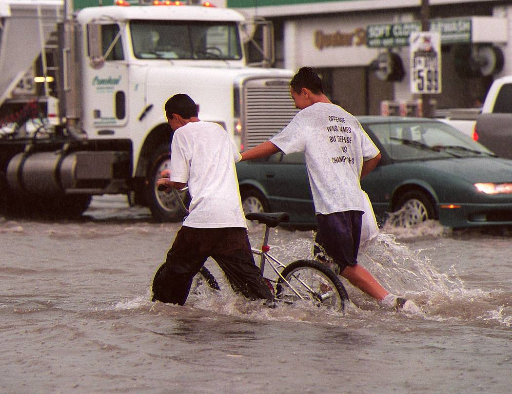 Two boys push a bicycle through the intersection of Charleston and Lamb on Thursday, July 8, 19 ...