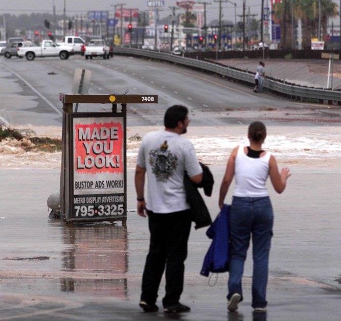 On lookers watch the flood waters crossing Boulder Highway near Sahara. (Las Vegas Review-Journ ...