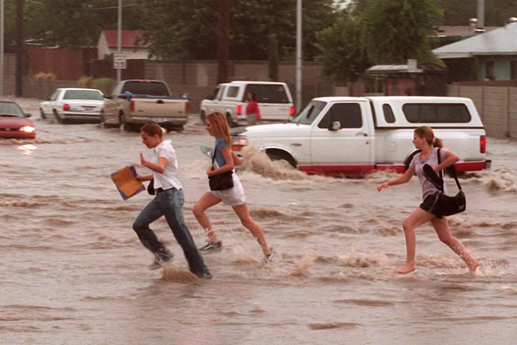 School Kids cross a flooded street near Washington and Pecos. (Las Vegas Review-Journal)