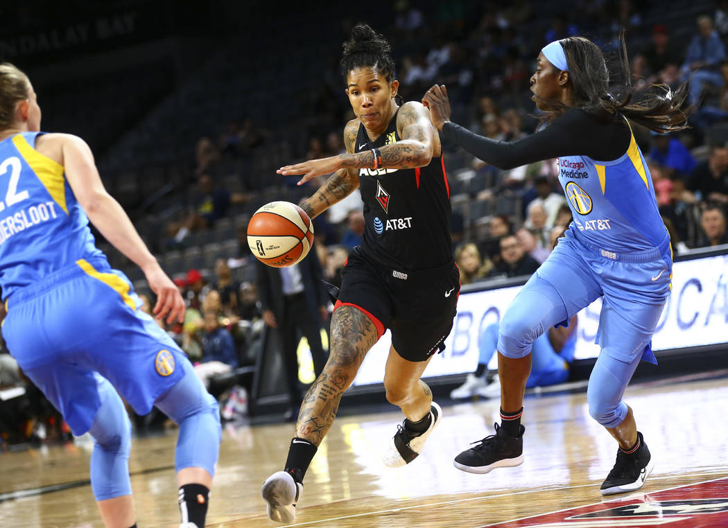 Las Vegas Aces' Tamera Young, center, drives to the basket against Chicago Sky's Kahleah Copper ...