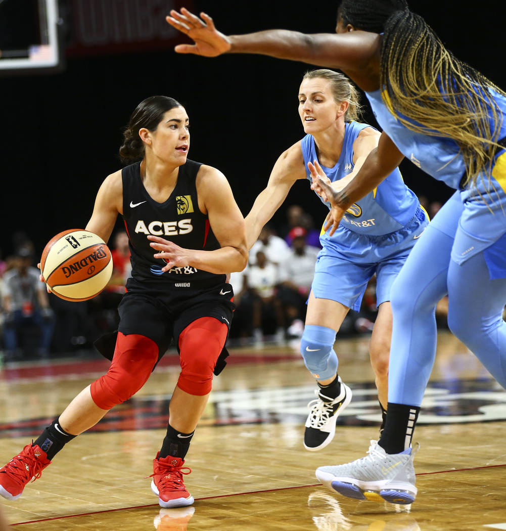 Las Vegas Aces' Kelsey Plum drives the ball under pressure from Chicago Sky's Allie Quigley dur ...