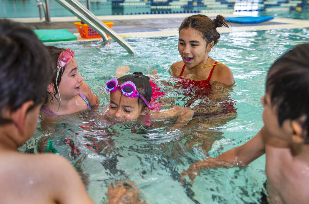 Lorelai Zimring, 5, left, and Ariana Villeda, 4, center, work with swim instructor Shanneal Ocu ...