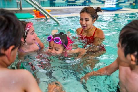 Lorelai Zimring, 5, left, and Ariana Villeda, 4, center, work with swim instructor Shanneal Ocu ...