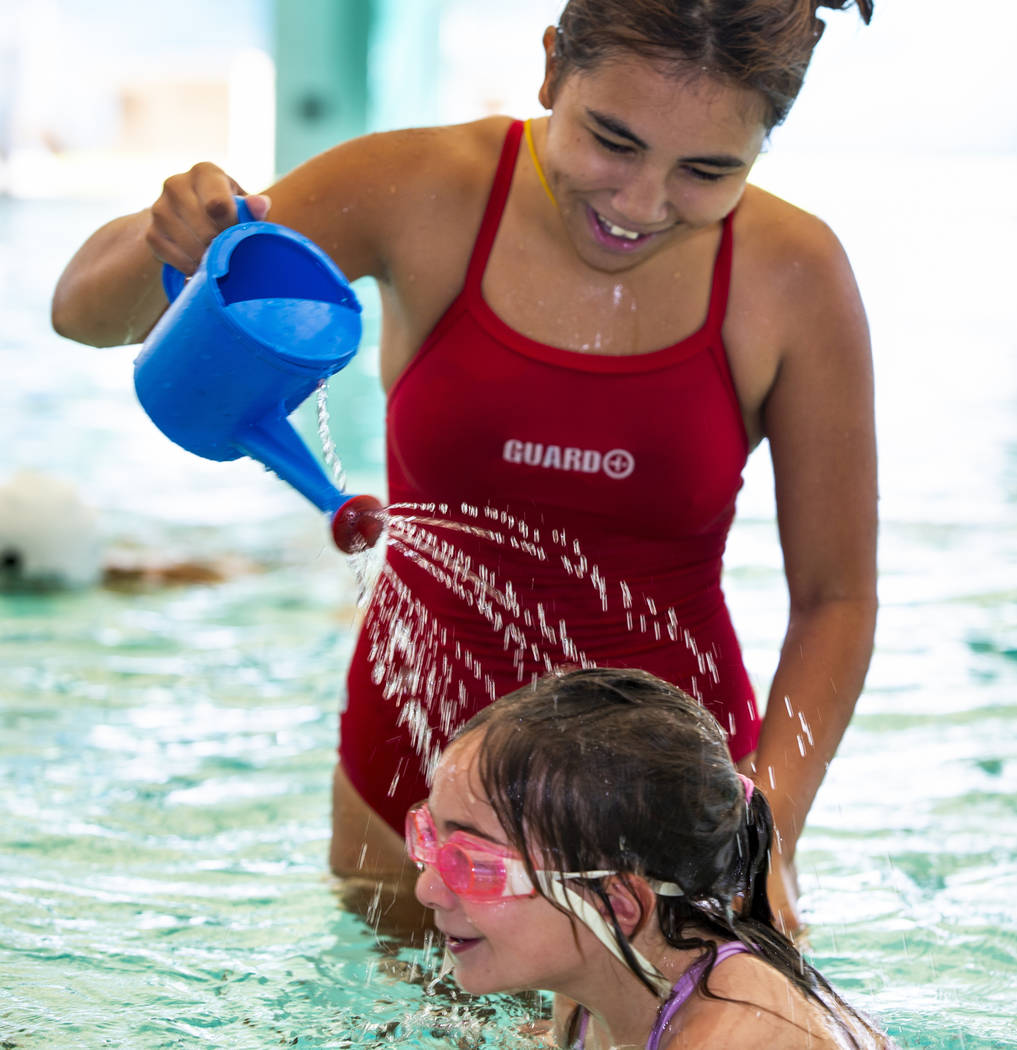 Swim instructor Shanneal Ocular, top, sprinkles water on the head of her student Lorelai Zimrin ...