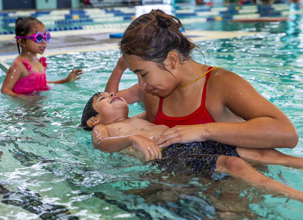 Swim instructor Shanneal Ocular, right, helps her student Stefan Flores, 4, to float during a b ...