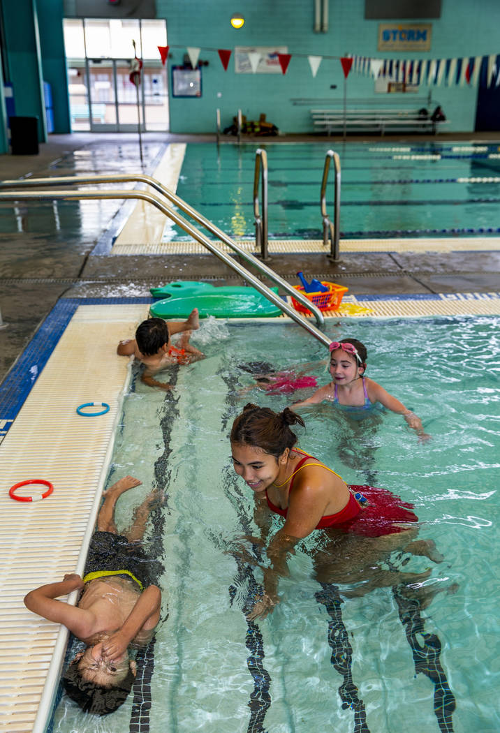 Swim instructor Shanneal Ocular, center, watches her students Stefan Flores, 4, foreground, try ...