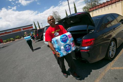 Las Vegas resident Randy Davis makes a water donation to Metro Pizza during a water bottle driv ...