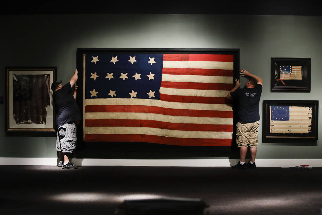 In this Wednesday, June 12, 2019 photo, workmen hang a Federal Era flag as part of the new exhi ...
