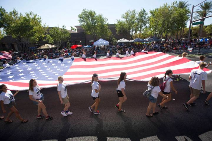Members of the Palo Verde High School track team march with a giant American Flag during the Su ...