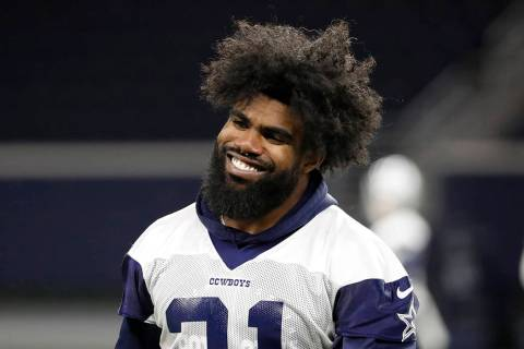 Dallas Cowboys running back Ezekiel Elliott smiles as he walks off the field after participatin ...