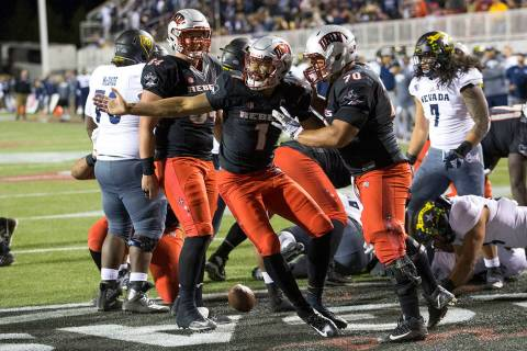 UNLV Rebels quarterback Armani Rogers (1), center, celebrates with offensive lineman Sid Acosta ...