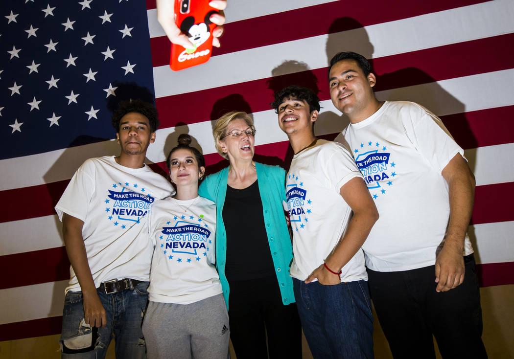 Democratic presidential candidate Sen. Elizabeth Warren, D-Mass., center, poses with members of ...