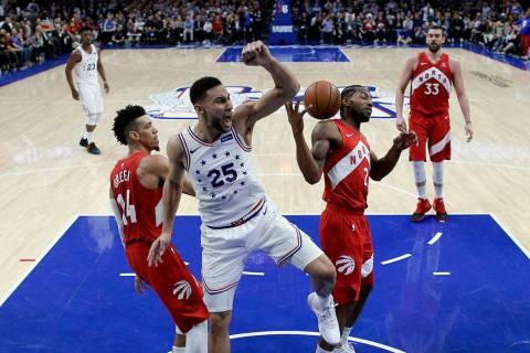 Philadelphia 76ers' Ben Simmons (25) reacts after dunking the ball between Toronto Raptors' Dan ...