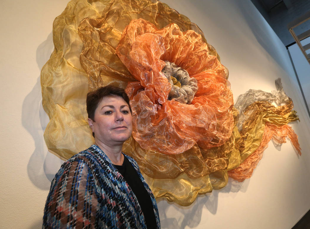 Denise Duarte in front of her sculpture entitled 'The Rosette' at Sahara West Library Art Galle ...