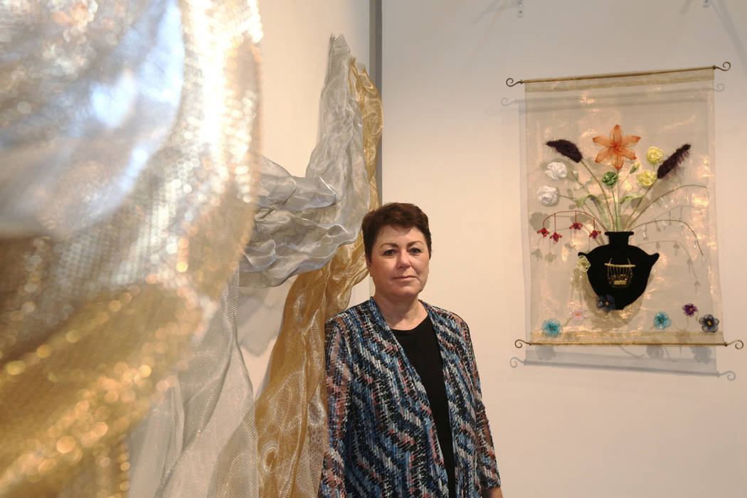 """Denise Duarte in front of her sculptures """"Unraveling Identity,"""" left, and """"Flora Varietas,"""" at ..."""