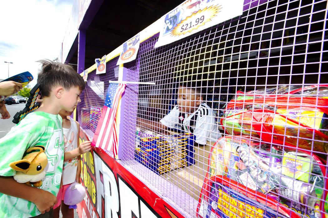 Evan Speas, 8, left, and Abigail Speas, 5, background, looks at fireworks as Bryce Jordan, 7, r ...