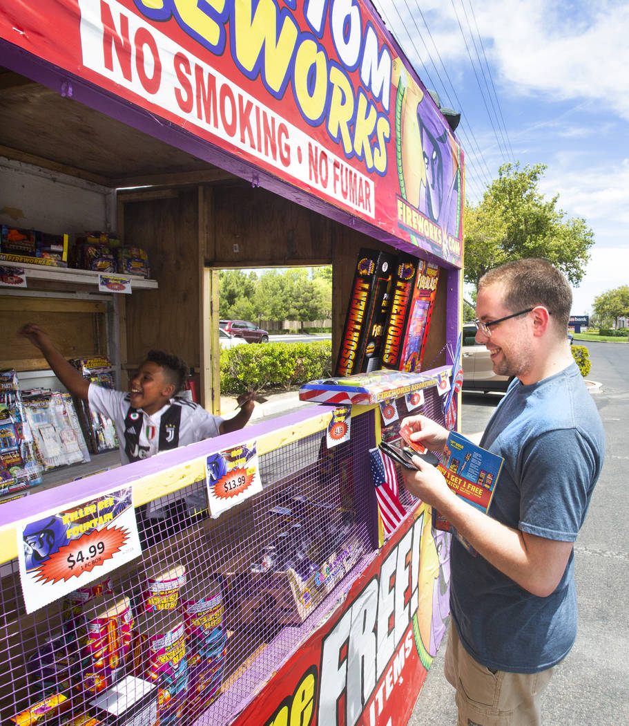 Bryce Jordan, 7, left, celebrates after Tim Meador, right, purchases fireworks on July 3, 2019, ...