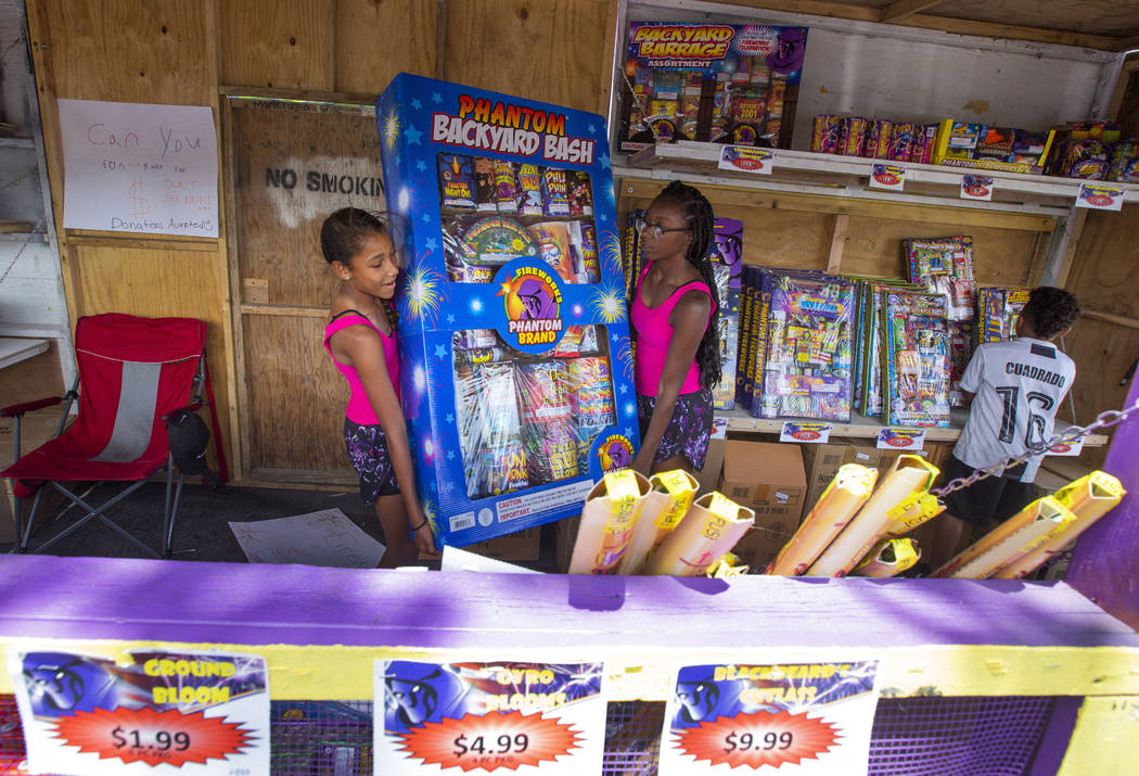 Ava Jordan, 11, left, and her sister Isaiah Jordan, right, 14, help move a box of fireworks whi ...