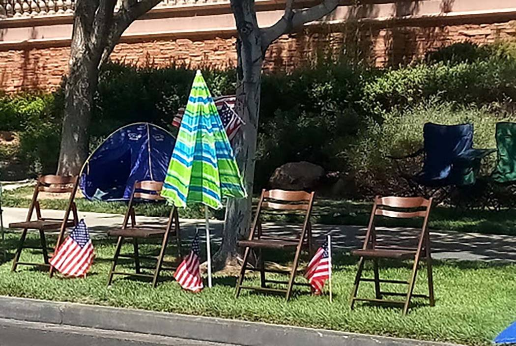 Wooden chairs, an umbrella and U.S. flags mark the spot where a family will watch the 25th annu ...