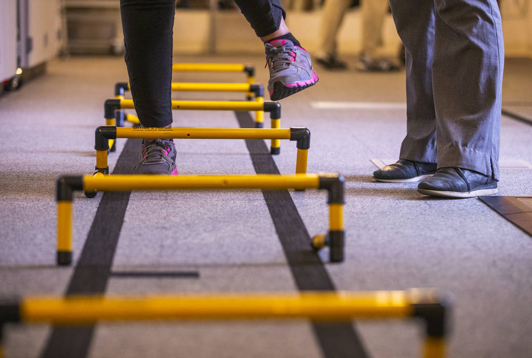 A patient steps over small hurdles within the physical therapy department at the Cleveland Clin ...