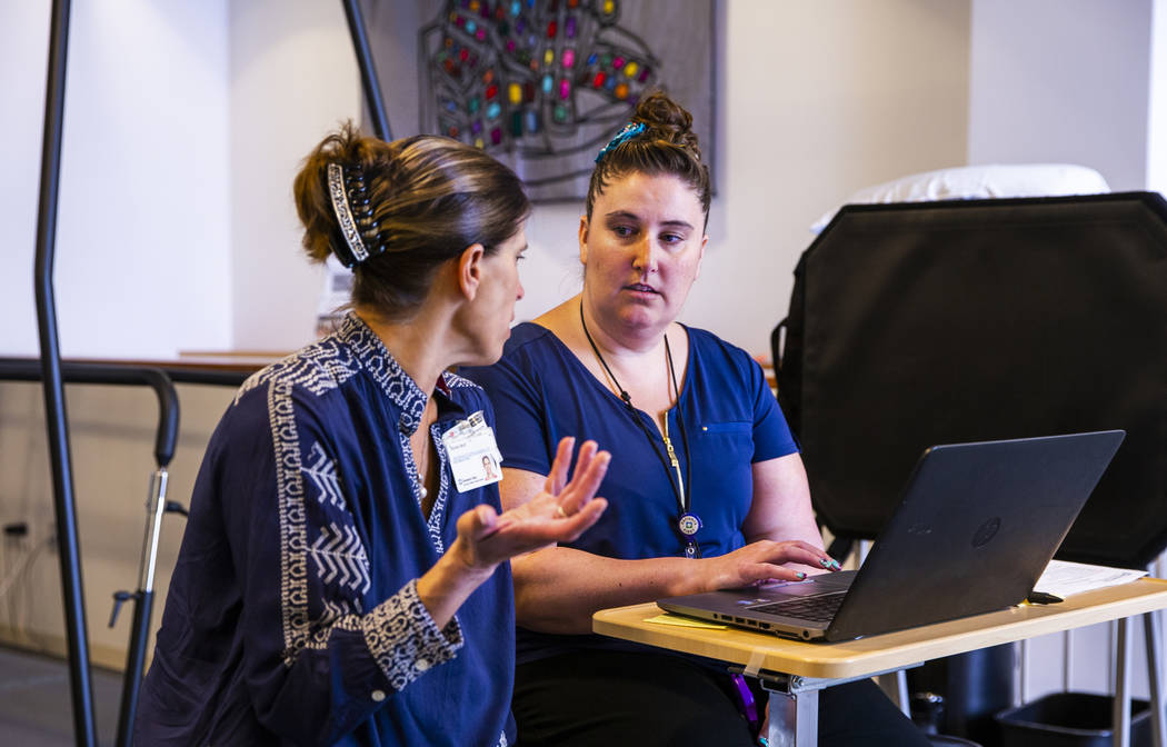 Marketing and Communications Director Nicole Wolf consults with Physical Therapist Sondi Facer ...