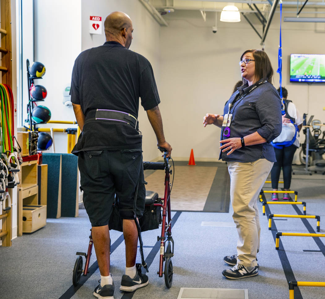 A patient confers with Physical Therapist Christine Ross on a walking exercise within the thera ...