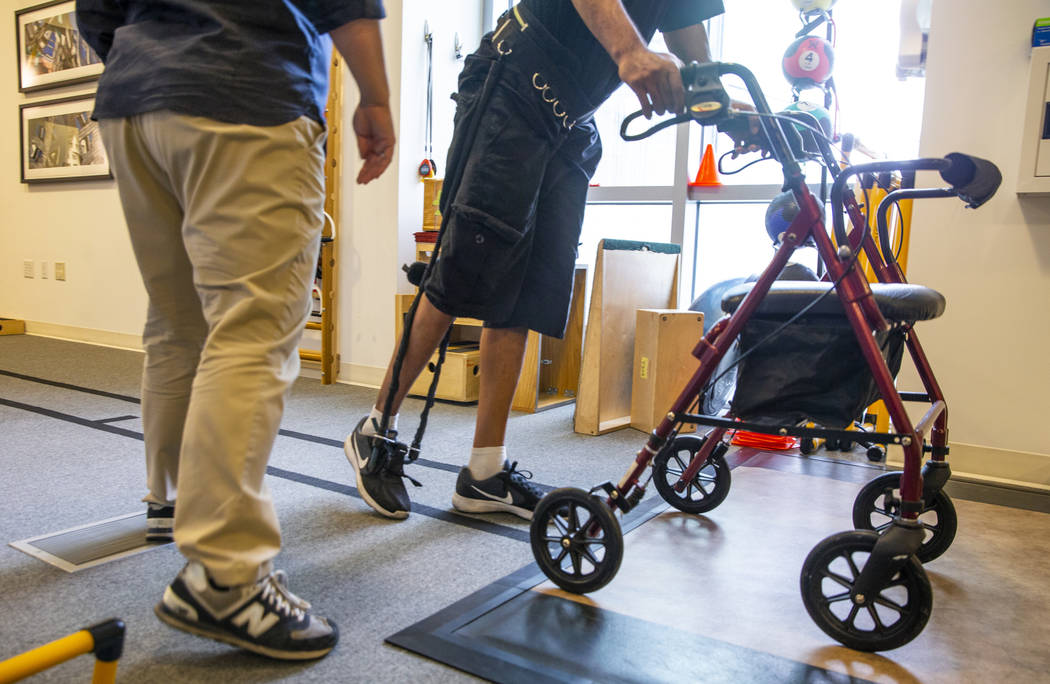 Physical Therapist Christine Ross works with a patient on a walking exercise within the therapy ...