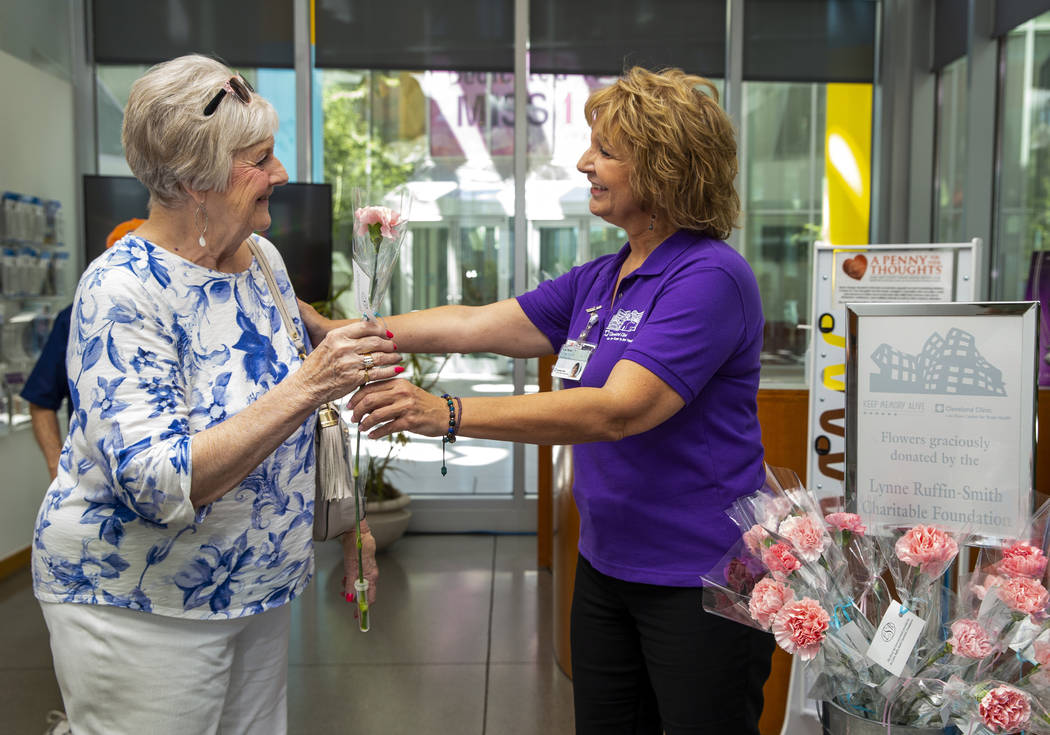 Patient Ann Ayton receives a flower after her appointment from volunteer/patient Lisa Naves at ...