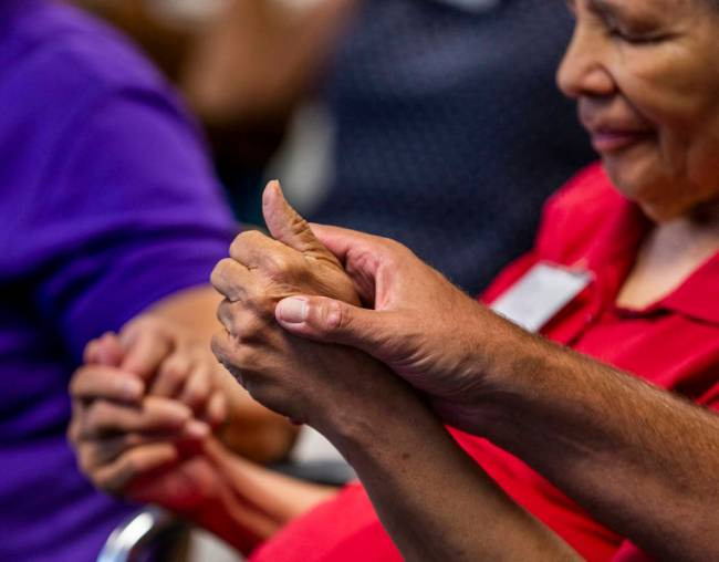 Participant Annie Hutchinson has her hand held by others during group exercises amongst songs, ...