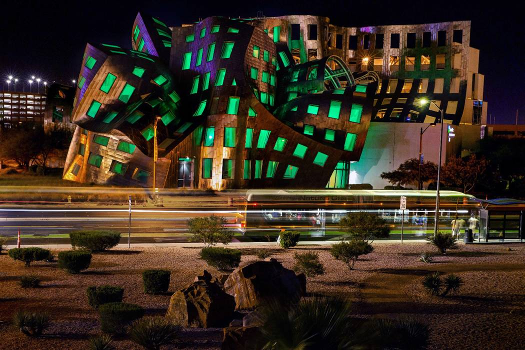 The windows are bathed in green from within the Keep Memory Alive Event Center designed by reno ...