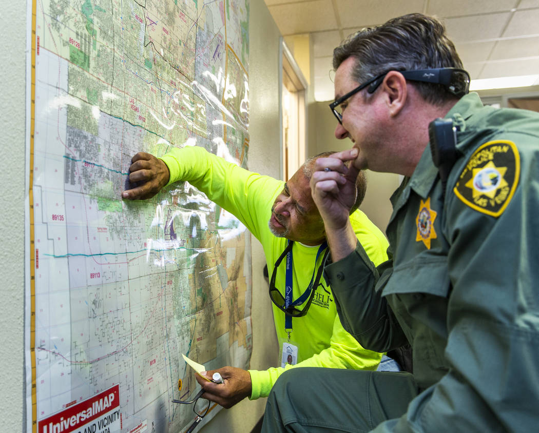 HELP of Southern Nevada Director of Crisis Teams Louis Lacey, left, confers with Metropolitan P ...