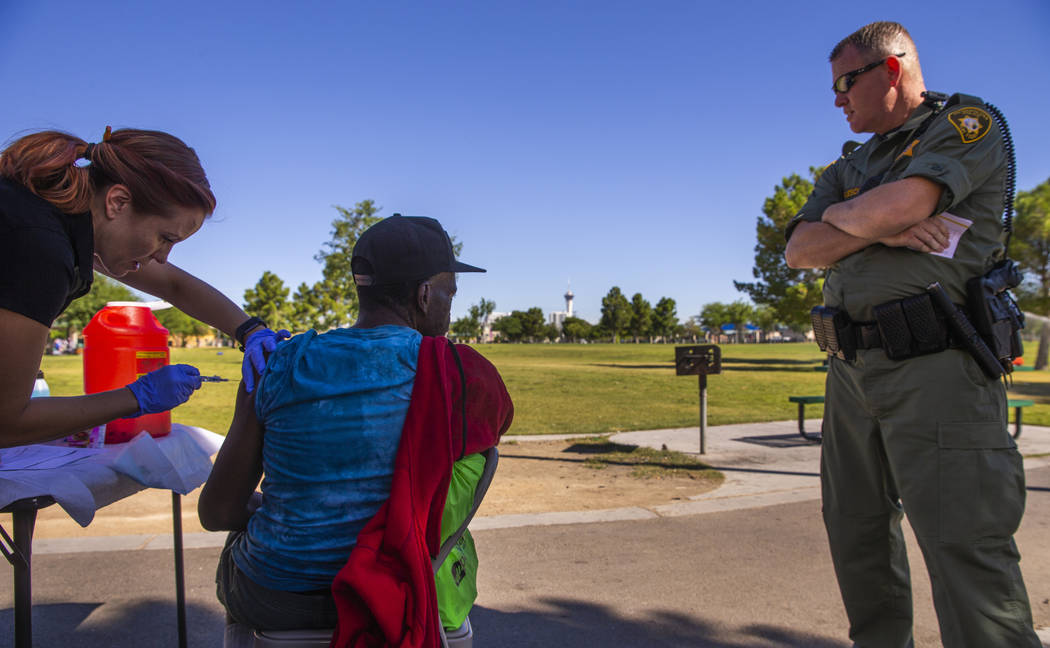 Sarah Lugo, Southern Nevada Health District senior community health nurse, gives a homeless man ...
