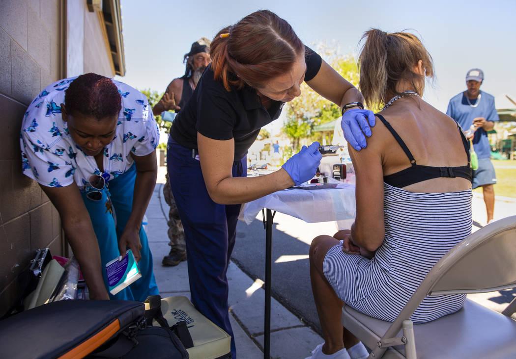 Sarah Lugo, Southern Nevada Health District senior community health nurse, center, gives homele ...